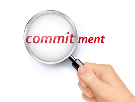 commitment: commitment word showing through magnifying glass held by hand