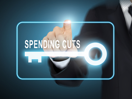 spending: male hand pressing spending cuts key button over blue abstract background