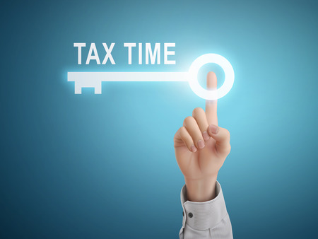 taxpayer: male hand pressing tax time key button over blue abstract background