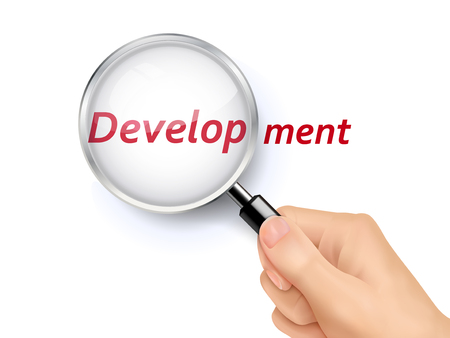 held: development word showing through magnifying glass held by hand