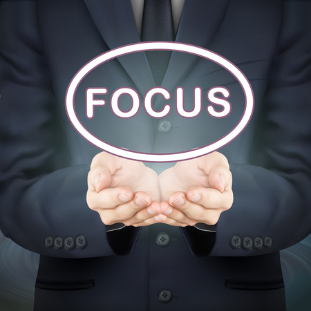 centralize: close-up look at businessman holding focus word