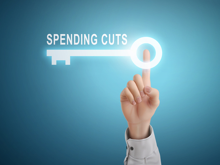 cutback: male hand pressing spending cuts key button over blue abstract background