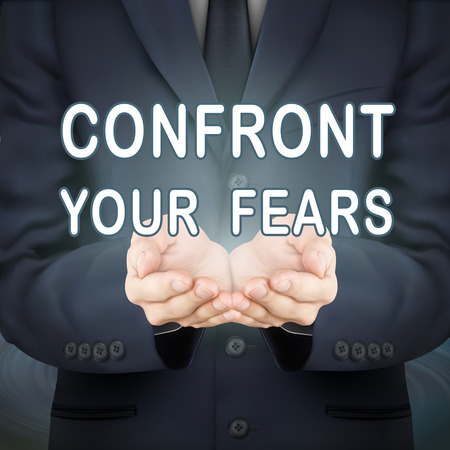 confront: close-up look at businessman holding confront your fears words
