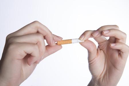 No smoking concept, closeup of hands holding cigarette, no smoking sign