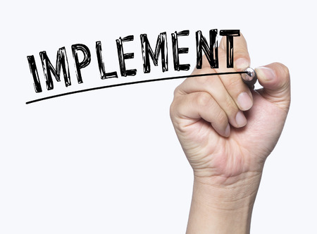 implement: implement written by hand, hand writing on transparent board, photo Stock Photo