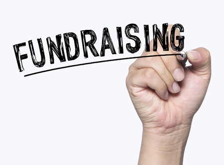 raise hand: fundraising written by hand, hand writing on transparent board, photo Stock Photo