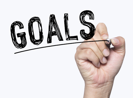 conquer: goals written by hand, hand writing on transparent board, photo Stock Photo