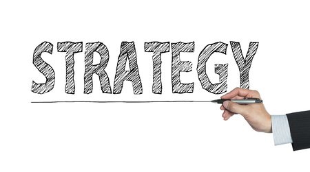 crucial: strategy written by hand, hand writing on transparent board, photo Stock Photo