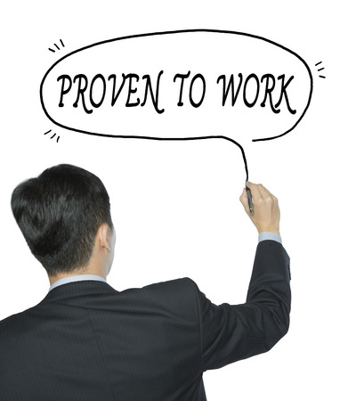 proven: proven to work written by businessman in black suit, hand writing on transparent board, photo Stock Photo