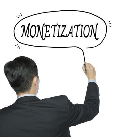 monetization: monetization written by businessman in black suit, hand writing on transparent board, photo