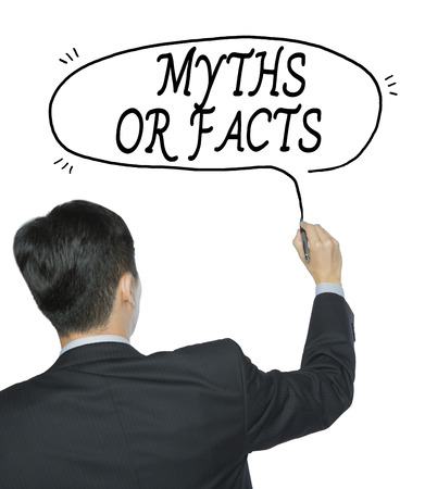 myths or facts written by businessman in black suit, hand writing on transparent board, photo Stock Photo