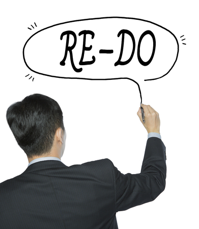 re design: re do written by businessman in black suit, hand writing on transparent board, photo