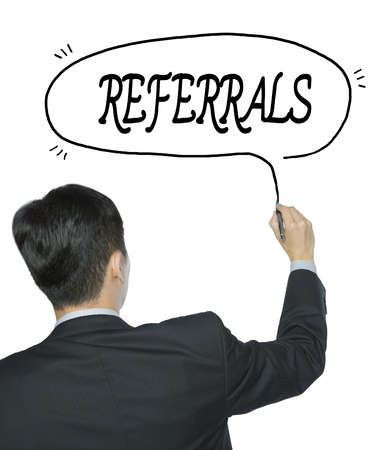 referidos: referrals written by businessman in black suit, hand writing on transparent board, photo Foto de archivo