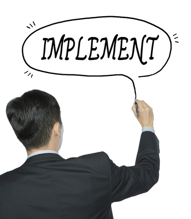 implement written by businessman in black suit, hand writing on transparent board, photo