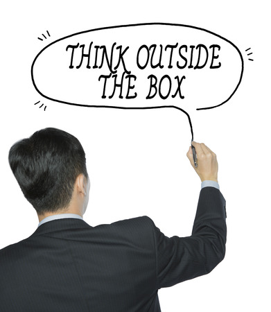 unconventionally: think outside the box written by businessman in black suit, hand writing on transparent board, photo