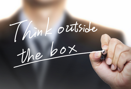 unconventionally: think outside the box written by hand, hand writing on transparent board, photo Stock Photo