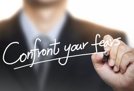 confront your fears written by hand, hand writing on transparent board, photo Stock Photo