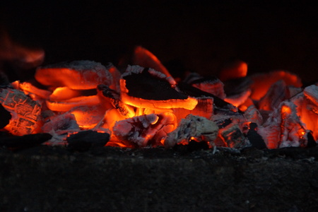 Embers with flames in the barbecue. Front view, in outside and without character. The embers have a beautiful yellow, bright orange color.