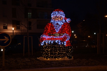 A great Santa Claus illuminated, in the night. It's front, there's nobody around. The lights are red and white, they are the colors of the folk character. We feel the Christmas atmosphere completely.