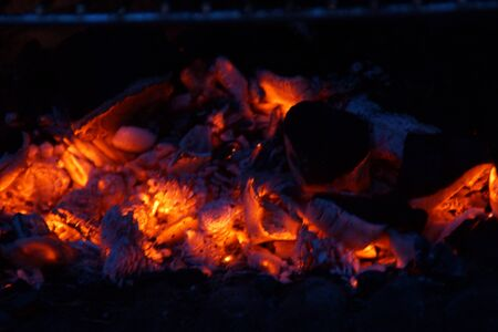 Embers in the barbecue, with an orange bright color. Front view, in outside and without character.
