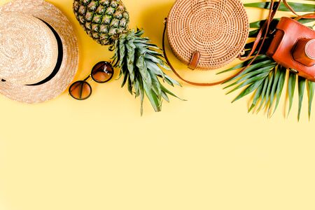 Womens accessories traveler: bamboo bag, straw hat, tropical palm leaves monstera, retro camera on yellow background. Flat lay, top view