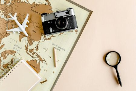 Planning vacation, travel plan, trip vacation using world map along with other travel accessories. Top view, flat lay.