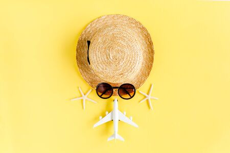 Tourist face made of straw hat, model plane, airplane and sunglasses on yellow background. Traveler accessories concept.