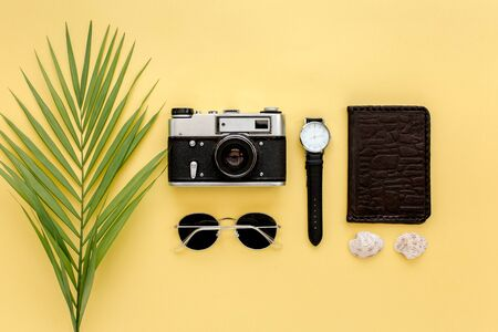 Traveler accessories on yellow background with palm leaf, camera and sunglasses. Flat lay, top view.