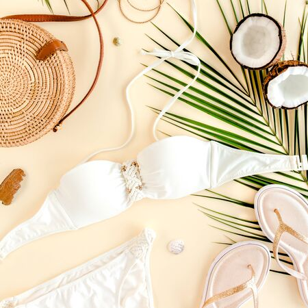 Womans beach accessories: bikini, rattan bag, straw hat, tropical palm leaves on yellow background. Summer background.