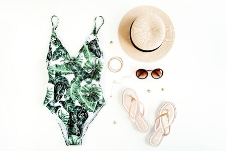 Womans beach accessories: swimsuit with tropical print, straw hat on white background. Summer background.
