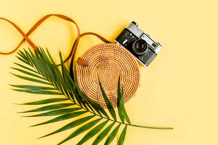 Traveler accessories concept on yellow background. Fashionable handmade natural round rattan bag, retro camera and tropical leaves. Archivio Fotografico