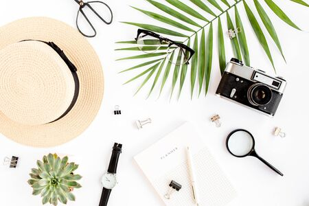 Top view home office desk. Workspace with straw hat, glasses, retro camera, notepad and tropical palm leaf on white background. Flat lay, top view. Standard-Bild