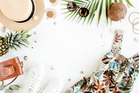 Female, summer street style. Womens frame of accessories. Sundress-dress, straw hat, sneakers, sunglasses, camera and pineapple. Top view, flat lay.