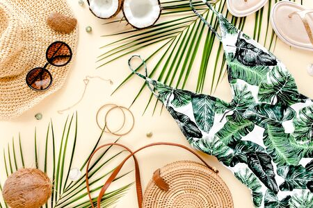 Woman's beach accessories: swimsuit with tropical print, rattan bag, straw hat, tropical palm leaves on yellow background. Summer background. Flat lay, top view. Archivio Fotografico