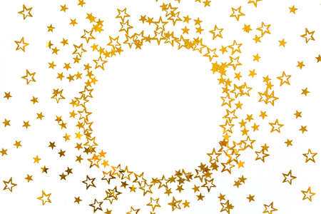 Round frame of gold stars confetti, glitter decoration on a white, festive background. Christmas or New Year pattern. Flat lay, top view Stock fotó