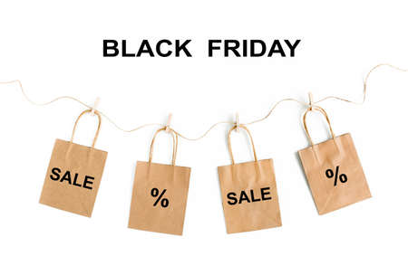 Black Friday sales discount concept. Craft paper bags with word Sale on white background.