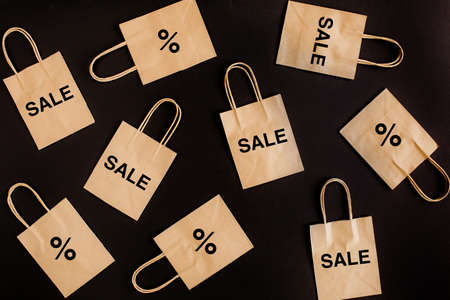Black Friday sales discount concept. Craft paper bags with word Sale on black background. Stock Photo