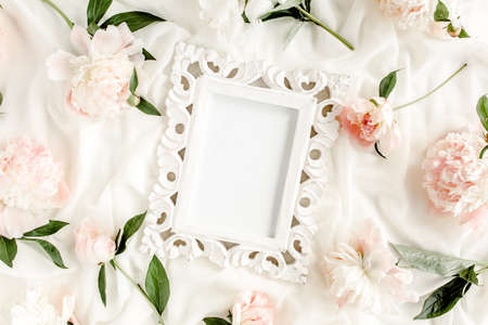 Carved, white frame decorated of beautiful and beige peonies. Flat lay, top view. Valentines background. Floral frame. Peony texture.
