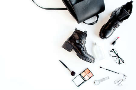Women fashion accessories on white background top view. Flat lay female style look with Black backpack and bots. Top view.