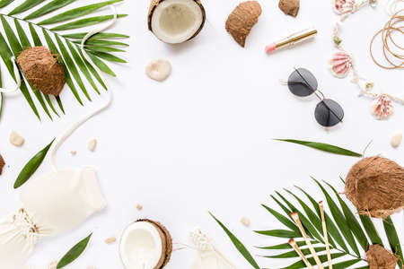 Feminine beige swimsuit beach accessories, tropical palm leaf branches, coconuts on white background with empty space for text. Flat lay, top view.