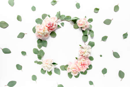 Floral round frame wreath made of pink and beige peonies flower buds, eucalyptus branches and leaves isolated on white background. Flat lay, top view. Standard-Bild