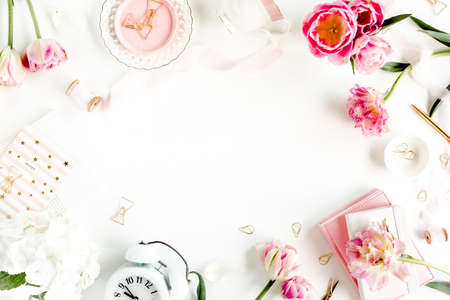 Fashion blog pink style desk with accessories, tulip flowers, scissors, coffee cup on white background. Flat lay. Top view.