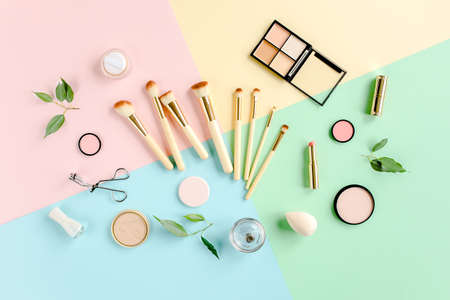 Professional decorative cosmetics and makeup tools brushes on colorful background. Beauty and fashion concept. Flat lay composition. Top view.