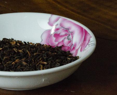 Assam mangalam looseleaf tea in flowered bowl Stock Photo