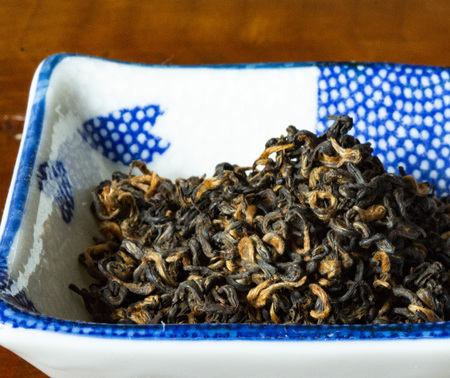 black looseleaf tea in a blue and white bowl