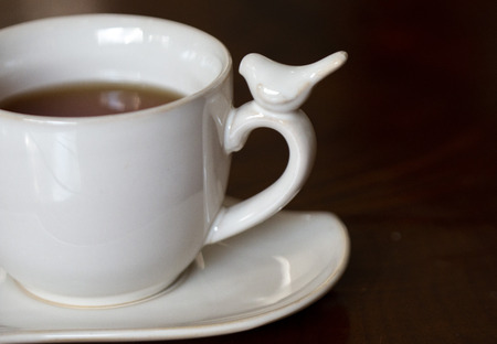 cup of tea in a white porcelain cup with a little bird Banco de Imagens - 115031753