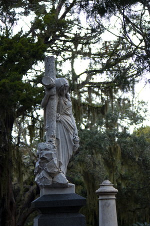 Weary woman leaning on cross statute at graveyard