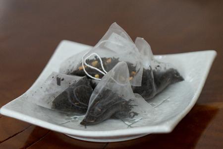 Black tea pyramid bags (sachets) Archivio Fotografico - 115031770