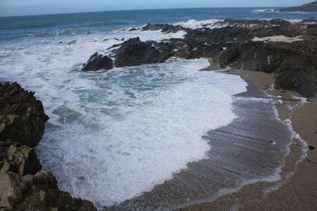 The sea rushing into a beach cove photo