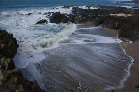 The waves rushing along a beach in Newquay photo